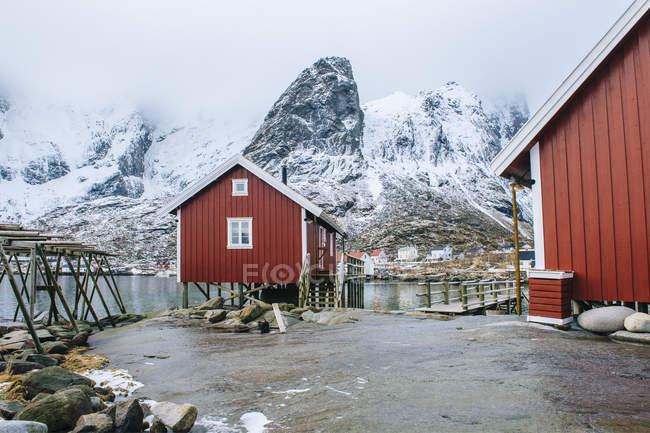 Cabanas de madeira de pesca vermelhas e neve-caped rochas, Reine, Lofoten, Noruega — Fotografia de Stock