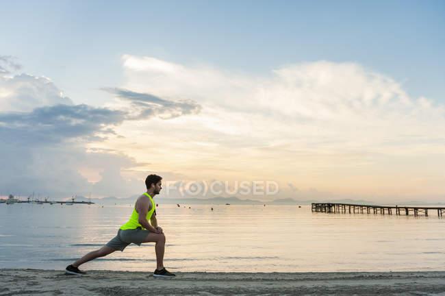 Vista lateral do homem lunging na praia, Mallorca, Espanha — Fotografia de Stock