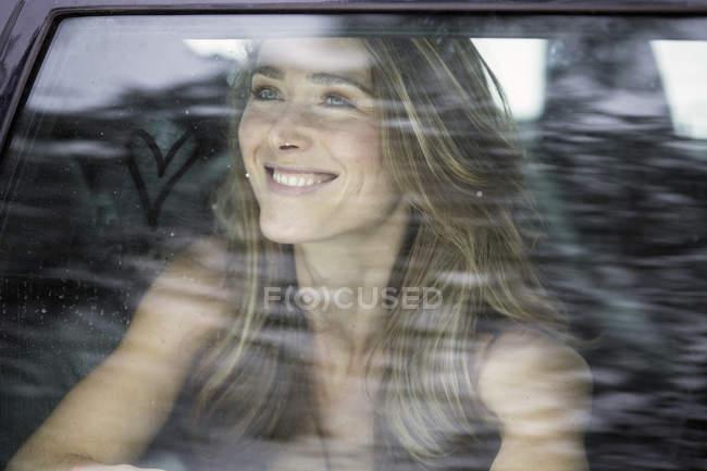 Mujer sonriente sentado dentro del vehículo - foto de stock