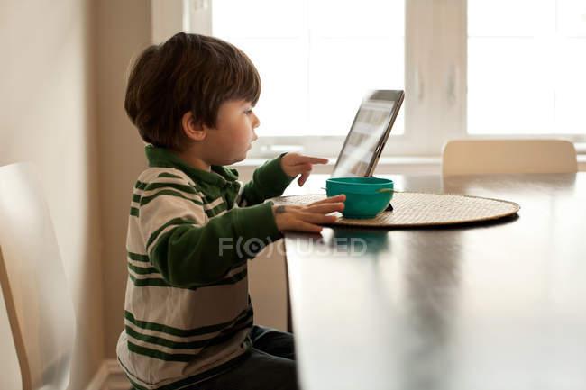 Ragazzo che utilizza tablet digitale a tavola — Foto stock