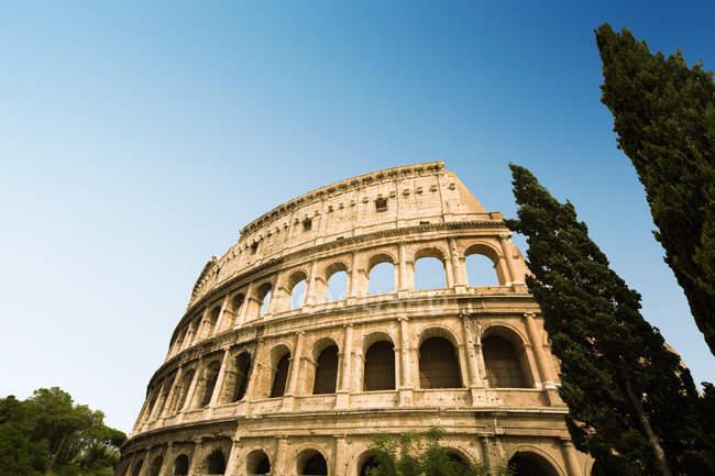 Низький кут зору Колізей з безхмарне небо на фоні, Рим, Італія — стокове фото