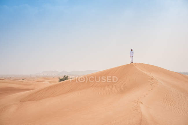 Young middle eastern man wearing traditional clothes looking out from desert dune, Dubai, United Arab Emirates — Stock Photo