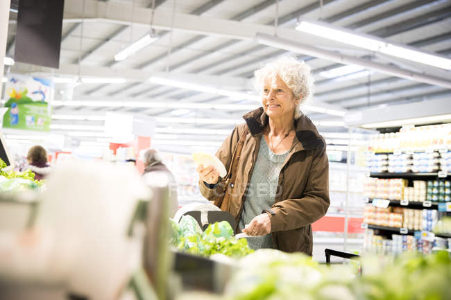 Mature woman in supermarket, looking at fresh produce — Stock Photo