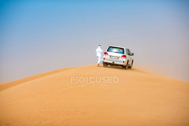 Middle eastern man wearing traditional clothes with off road vehicle parked on desert dune, Dubai, United Arab Emirates — Stock Photo