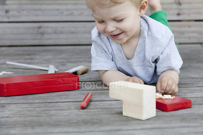 Male toddler playing with wooden blocks for toy boat on pier — Stock Photo