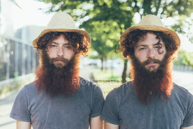 Portrait of identical male hipster twins wearing straw hats on sidewalk — Stock Photo