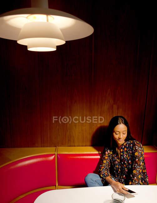 Donna che si siede in legno con pannelli stand guardando smartphone — Foto stock