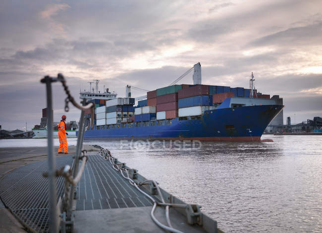 Trabalhador portuário e navio que entra no porto — Fotografia de Stock