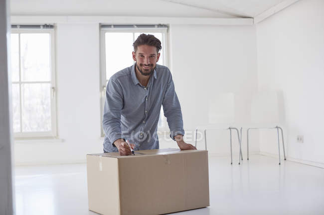 Portrait of young man writing on cardboard box whilst moving house — Stock Photo
