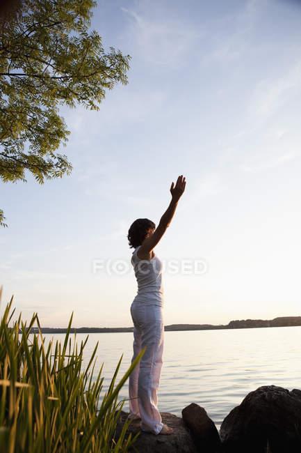 Женщина, исполняющая йогу на озере — стоковое фото