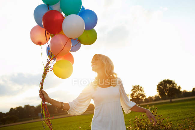 Girl with balloons outside at sunset — Stock Photo