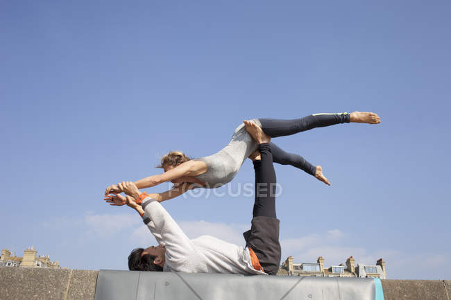 Man and woman practicing acrobatic yoga on wall — Stock Photo