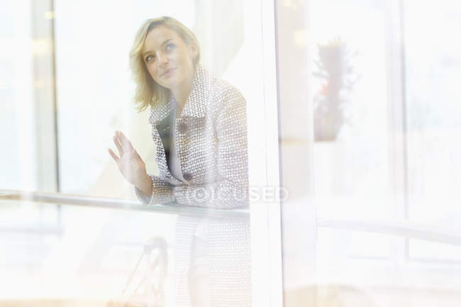 Mid adult woman looking through shopping centre window — Stock Photo