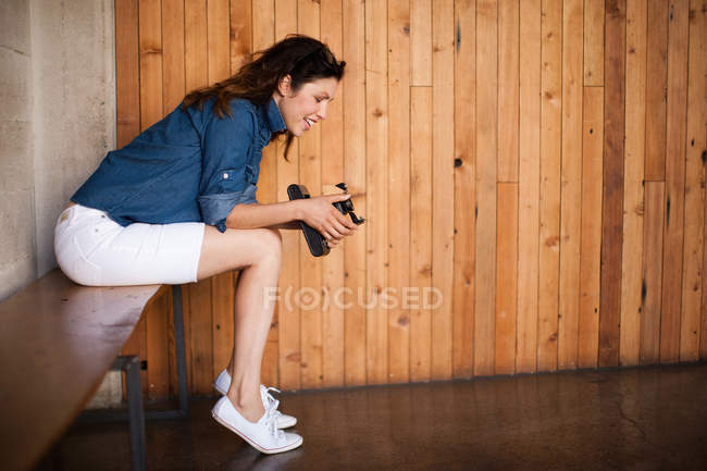 Mid adult woman using vintage medium format camera — Stock Photo