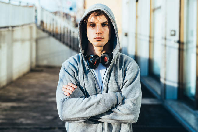 Man wearing hooded top and headphones, arms crossed looking at camera — Stock Photo