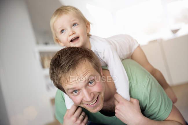 Посміхаючись Отця, несучи хлопчика на спині — стокове фото