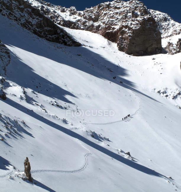 Paesaggio di montagna innevate con distante gruppo di escursionisti — Foto stock