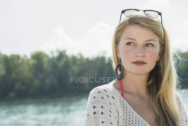 Young woman with long blonde hair looking away, portrait — Stock Photo