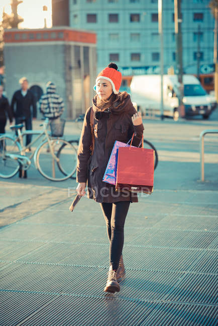 Mid adult woman wearing red pom pom hat strolling with shopping bags — Stock Photo