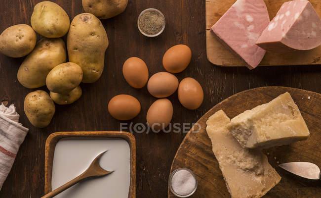 Vista superiore del cibo crudo e preparato, parmigiano, latte, uova e patate — Foto stock