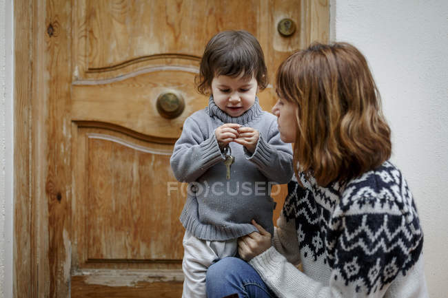 Mother and girl in front of wooden door — Stock Photo