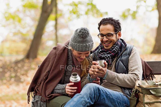 Пара пьющих кофе на скамейке в парке — стоковое фото
