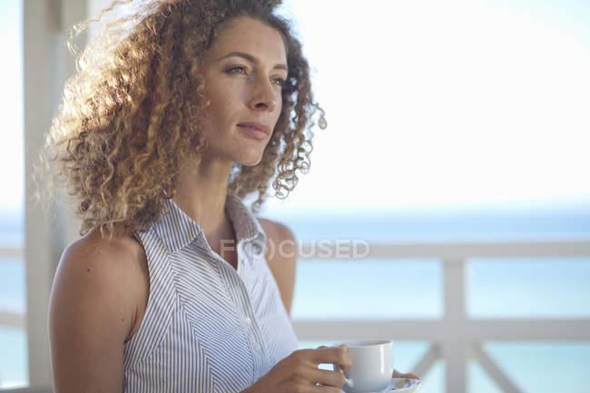 Junge Frau blicken hinaus auf das Meer vom Strand Haus Balkon — Stockfoto