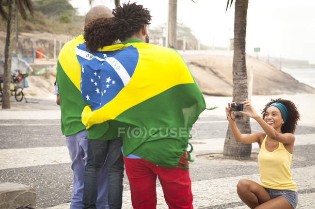 Young mother photographing family wrapped in Brazilian flag on Ipanema beach, Rio De Janeiro, Brazil — Stock Photo