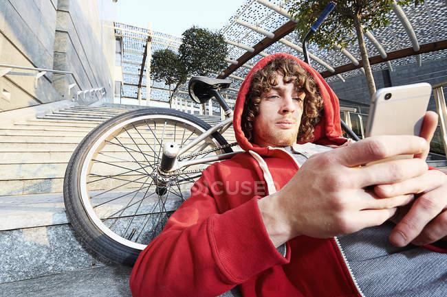 Homme assis sur les marches avec BMX à l'aide d'un smartphone — Photo de stock