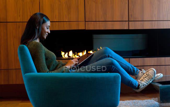 Femme dans le fauteuil devant les armoires en bois et feu ouvert, en utilisant une tablette numérique — Photo de stock