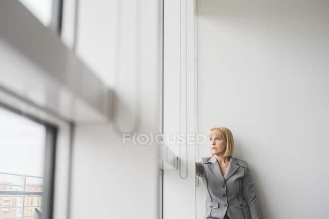 Зрілі бізнес-леді дивлячись через вікна офісу — стокове фото