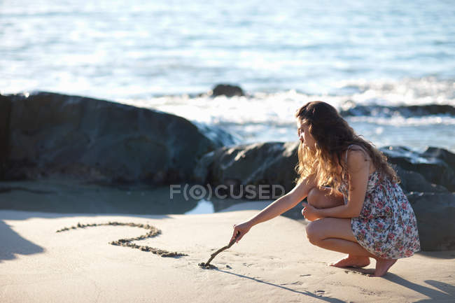 Женщина рисует вопросительный знак на песке — стоковое фото