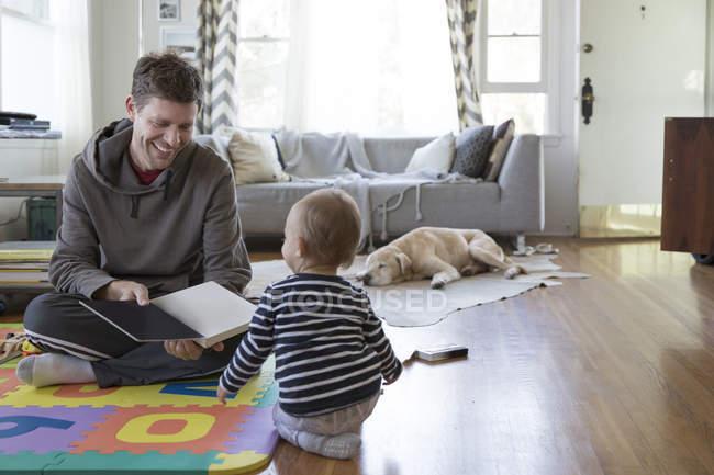 Отец и маленький сын дома, играют — стоковое фото