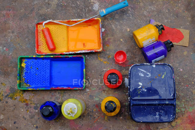 Top view of blue and yellow paint trays and paint roller — Stock Photo