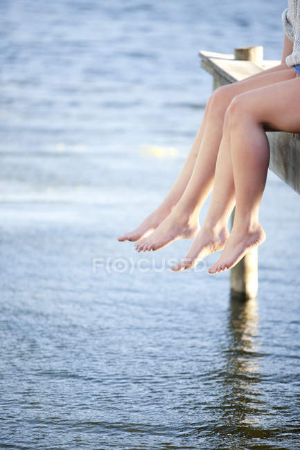 Two pairs of female legs dangling from pier — Stock Photo