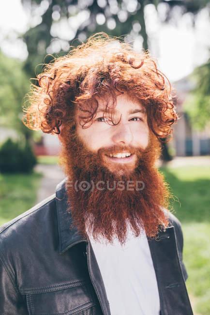 Retrato de jovem hipster masculino com cabelo encaracolado vermelho e barba no parque — Fotografia de Stock