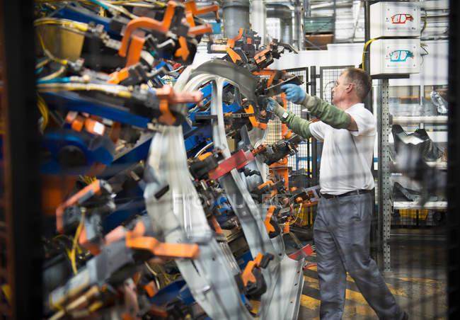 Lavoratore che maneggia le parti dell'automobile nella fabbrica dell'automobile — Foto stock