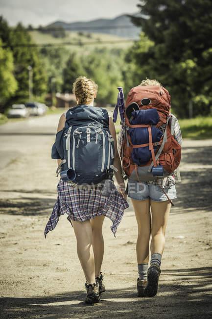 Vista posteriore di adolescente e giovane escursionista donna escursioni su strada rurale, Red Lodge, Montana, Stati Uniti d'America — Foto stock
