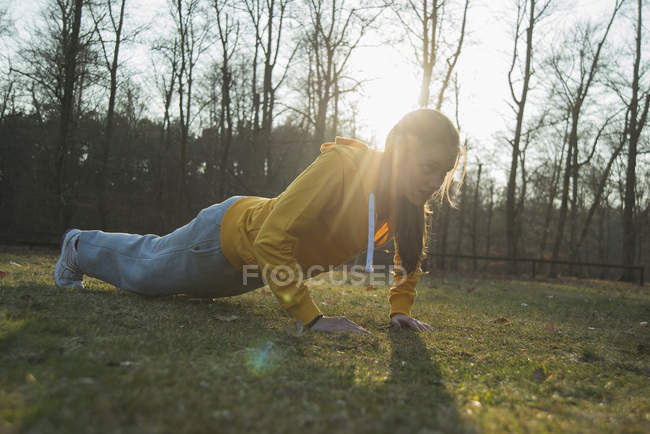 Young female runner doing warming push-ups in field — Stock Photo