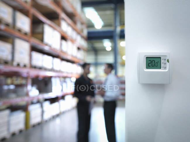 Сотрудники, работающие рядом с термостатом на заводе — стоковое фото