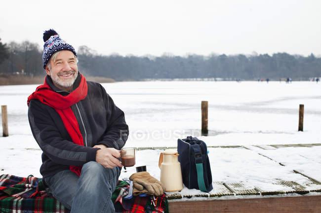 Uomo seduto sul molo con bevanda calda — Foto stock