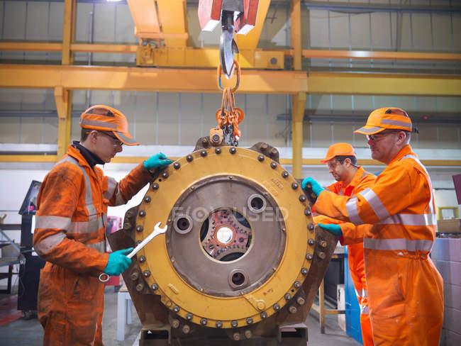 Ученик инженера и инженера, работающего над коробкой передач — стоковое фото