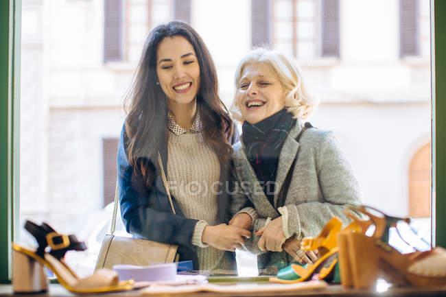 Blick durchs Schaufenster von Mutter und Tochter Arm in Arm Damenschuhe Lächeln betrachten — Stockfoto