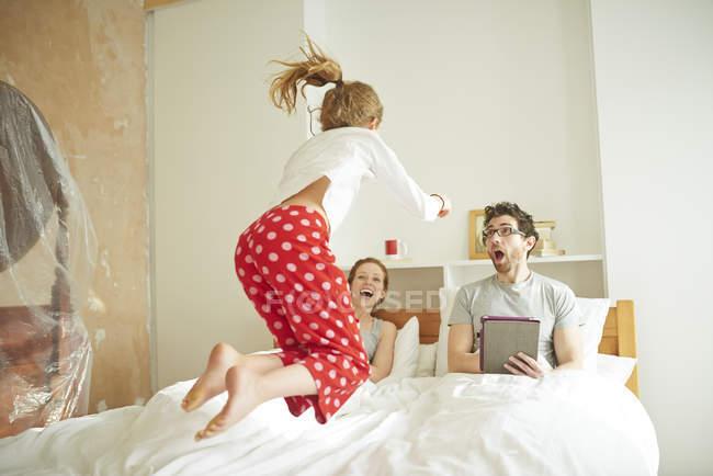 Pares adultos meados de ter a mentira dentro enquanto a filha salta na cama — Fotografia de Stock