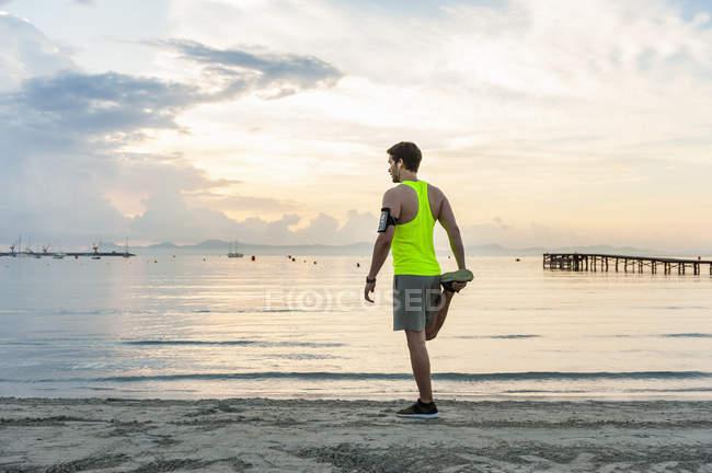 Vista traseira do homem esticar a perna na praia, Mallorca, Espanha — Fotografia de Stock