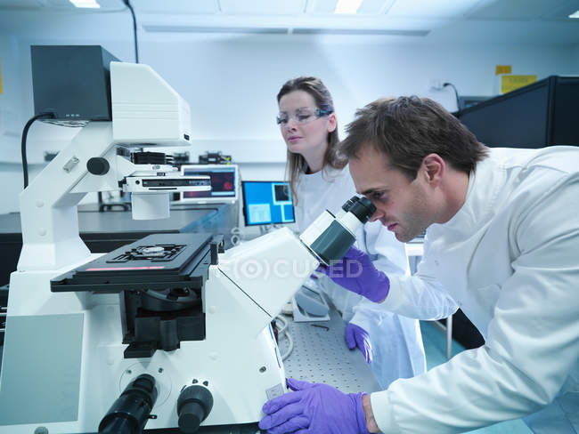 Scientists in lab coats using laser microscope — Stock Photo