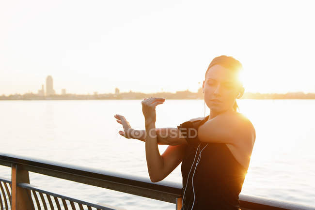 Giovane jogger femminile sul lungofiume guardando il lettore MP3 — Foto stock