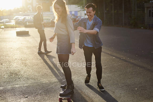 Young man pushing young female skateboarder on sunlit street — Stock Photo