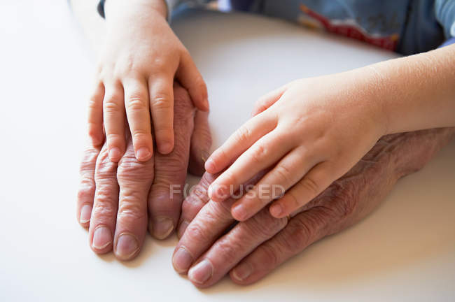 Hands of child and senior adult — Stock Photo