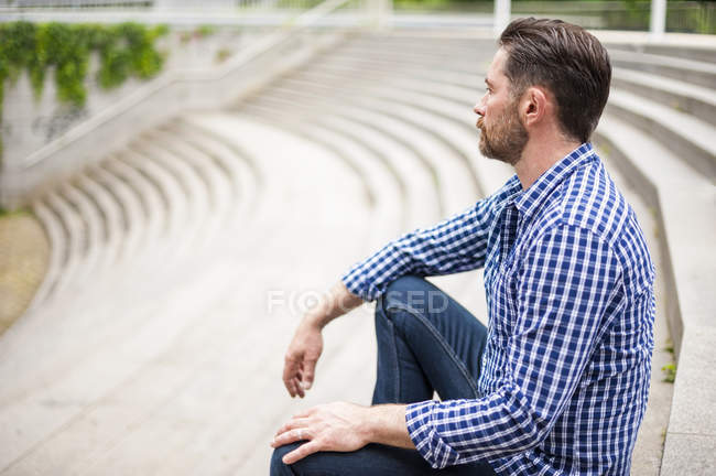 Mature man looking out from city stairway — Stock Photo